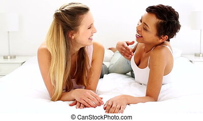 Two pretty friends chatting and lying on bed at home in...