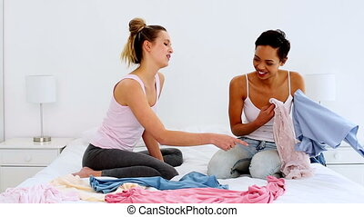 Two pretty friends jokingly fighting over clothes on bed at...