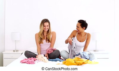 Two pretty friends throwing clothes