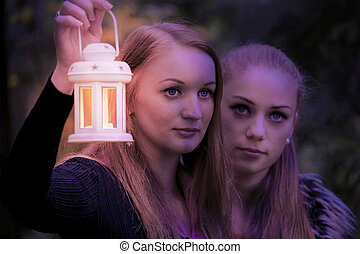 Two pretty girl in the dark with a lamp