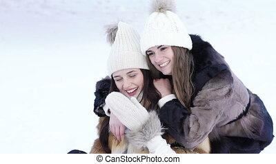 Two pretty girl posing for selfie in winter park. Slowly