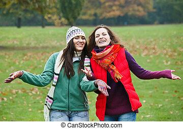 Two pretty girls having fun in autumn park