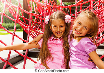 Two pretty girls hugging on rope of playground