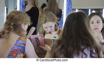 Two pretty girls sit in front of mirror and are apply cosmetics of their faces.