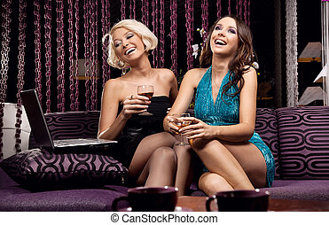 Two pretty girls watching something, smiling and drinking wine