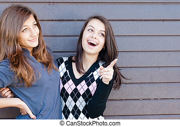 Two pretty happy Teen Girl Friends Laughing & pointing to copyspace