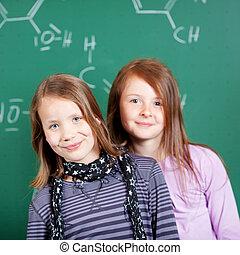 Two pretty little girls in school