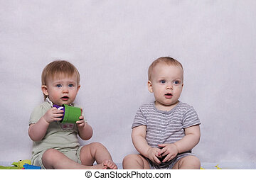 Two pretty little kids sitting with a toys in their hands