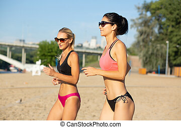 Two pretty middle-aged female joggers wearing sunglasses and swimsuit training at the beach
