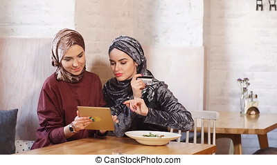 Two Pretty Muslim Woman Use Tablet in Cafe.