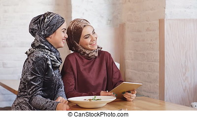 Two pretty muslim women with hijab in cafe. Sitting on...