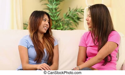 Two pretty sisters sitting on couch chatting in bright...