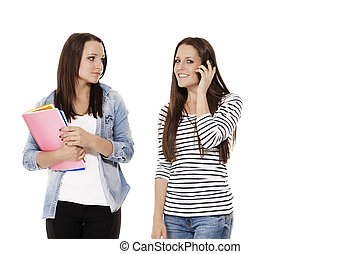 two pretty student friends calling by phone on white background