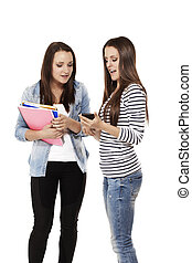 two pretty teenage students looking at a smartphone on white background