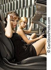 two pretty woman in black car