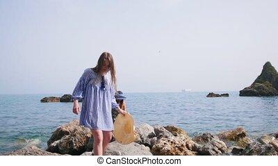 Two pretty women in beach attire walk along the stony shore...