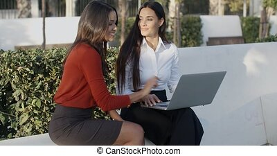 Two pretty women sharing a laptop outdoors - Two pretty ...