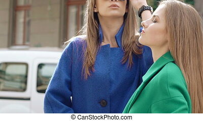 Two pretty women stand in pose in cashmere coats outdoor. Slowly