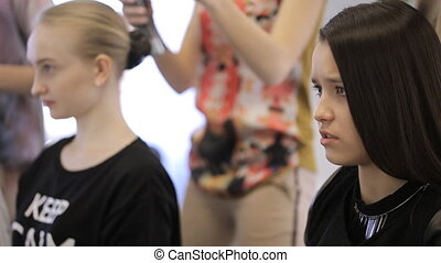 Two pretty young girls sit in beauty salon