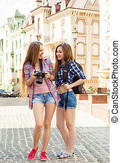 Two pretty young tourists looking at the screen of a camera ...