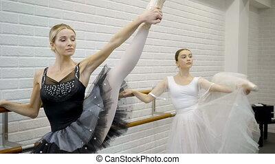 Two prima ballerinas stretch thier raised left legs standing...