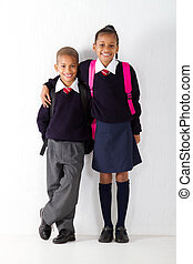 two primary pupils standing against classroom wall