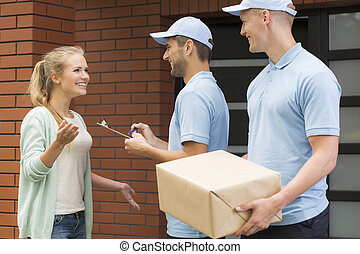 Two professional couriers delivering a package to a happy...