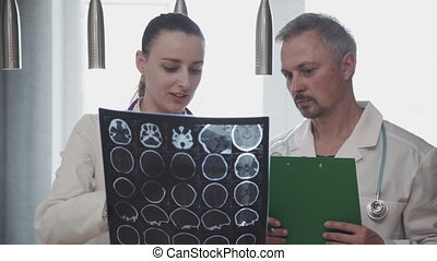 two professional doctor radiologist colleague discussing head brain skull x-ray shot. coworkers talking