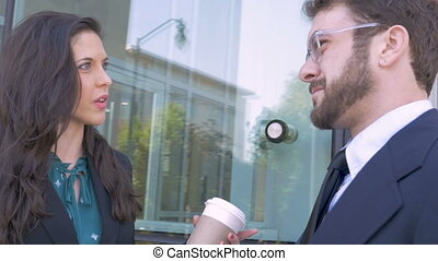 Two professional lawyers or businesspeople talking outside an office building