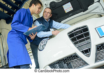 two professional mechanics inspecting car engine at their garage