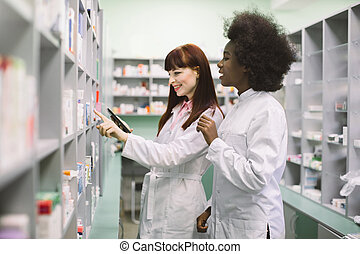 Two professional multiethnical pharmacists, African and Caucasian women, checking stock of medicines, using tablet, while standing at the shelve in modern drugstore