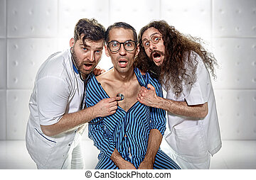 Two psychiatrists examining a funny lunatic