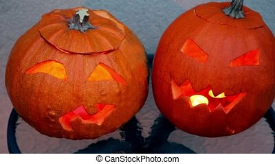 Two pumpkins of halloween lie on glass little table