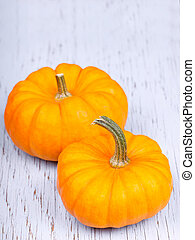 Two pumpkins on wooden background