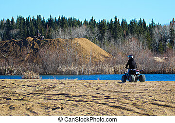 Two quaders take in the view of a pond while riding