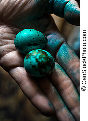 Two quail eggs painted blue on a paint stained woman's palm. Closeup view, selective focus