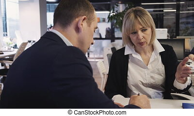 Two qualified, professional and ambitions businessperson in formal wear clothes working in modern workstation office with loft interior. Man and woman talking, discussing in meeting room