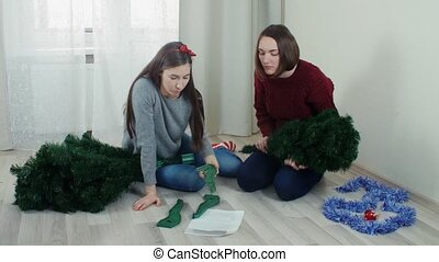 Two quarreling girls preparing Christmas tree for decorations