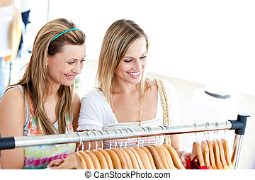 Two radiant women doing shopping  in a clothes shop