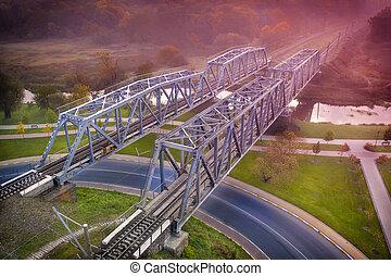 Two railway bridges across the river at dawn.
