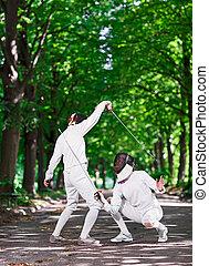 Two rapier fencers women fencing on park path