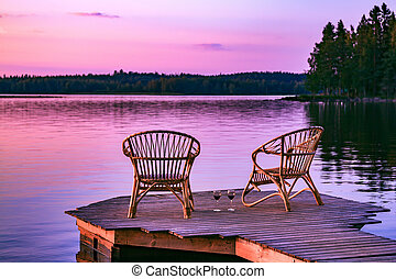 Two rattan chairs and glasses of red wine on a pier overlooking a lake at sunset in Finland