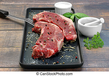 Two raw beef strip steaks on a black prep dish.  Selective focus on steak tip.