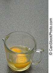 Two raw eggs in a measuring cup on a Grey worktop