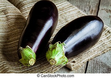 Two raw organic eggplant on sackcloth - Two raw organic...