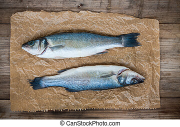 Two raw seabass fish on wooden background
