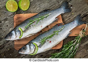 Two raw seabass with lime and rosemary on the wooden...