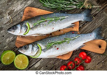 Two raw seabass with lime, cherry tomatoes and rosemary on...