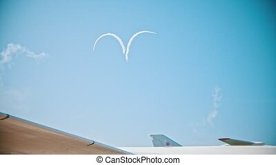Two reactive planes flying up drawing a heart in the sky with the smoke marks