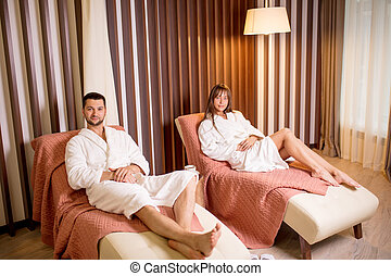 two reaxed young people in comfortable bathrobes resting on the armchairs